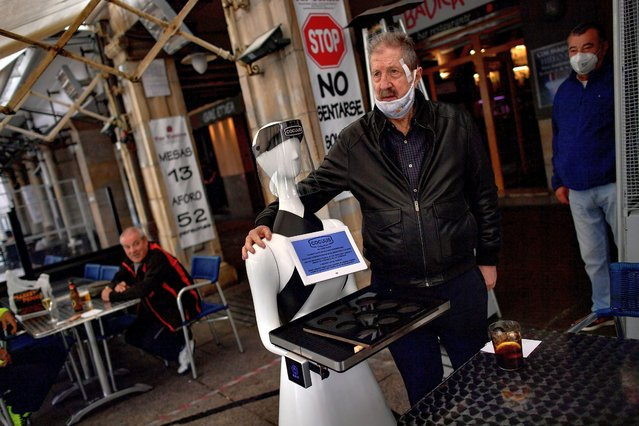 "A robot known as ""Alexia"" attends customers as one of them poses for a photograph with the robot in a bar at Plaza del Castillo square, in Pamplona, northern Spain, Friday, June 5, 2020. This robot tries to be an innovation to accept the new rules for all bars and restaurants by the crisis of the coronavirus. (Photo by Alvaro Barrientos/AP Photo)"