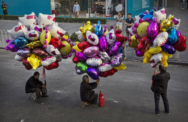 Chinese balloon sellers wait for customers in an outdoor shopping district on September 17, 2014 in Beijing, China. (Photo by Kevin Frayer/Getty Images)