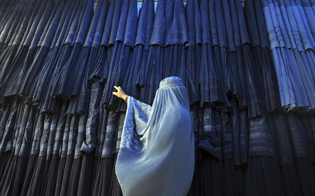 A woman clad in a burqa looks at other pieces of Afghanistan's traditional, all-encompassing dress at a store in Mazar-i Sharif, north of Kabul, Afghanistan, Thursday, September 10, 2015. (Photo by Mustafa Najafizada/AP Photo)