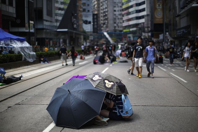 Protesters use umbrellas to shelter themselves from the sun as they block an area near the government headquarters building in Hong Kong, October 1, 2014. Thousands of pro-democracy protesters thronged the streets of Hong Kong early on Wednesday, ratcheting up pressure on the pro-Beijing government that has called the action illegal, with both sides marking uneasy National Day celebrations. (Photo by Carlos Barria/Reuters)