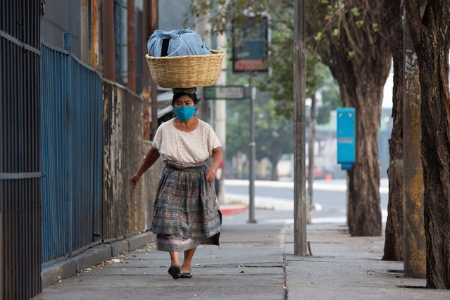 A street vendor walks along Bolivar Avenue, empty due to a total lockdown in Guatemala City, early Friday, May 15, 2020. The government decreed a three-day, nationwide lockdown starting Friday to help contain the spread of the new coronavirus. (Photo by Moises Castillo/AP Photo)
