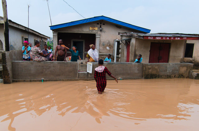 Nigerian people remove water from their house after heavy rains caused flood in Lagos, Nigeria on June 18, 2020. (Photo by Adeyinka Yusuf/Anadolu Agency via Getty Images)
