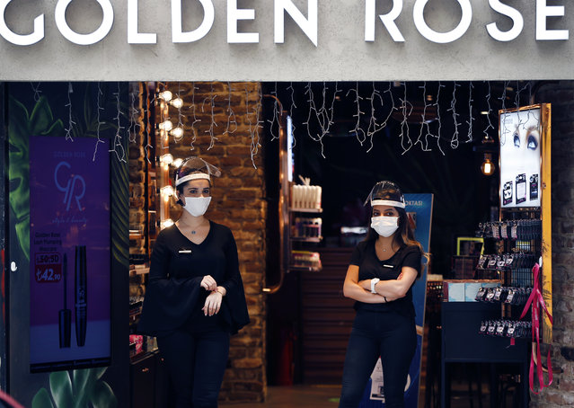 Shop employees, wearing protective masks and face shields against the spread of coronavirus, wait for customers on Istiklal street, the main shopping street in Istanbul, Thursday, June 18, 2020. (Photo by Emrah Gurel/AP Photo)