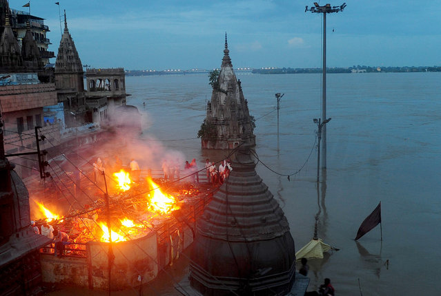 Indian mourners perform a cremation on the roof of a building overlooking The Manikarnika Ghat in Varanasi on August 23, 2016. India's holy city of Varanasi has been forced to halt cremations along the banks of the sacred river Ganges as deadly floods from monsoon rains hit parts of the country, an official said. More than 100,000 people have been forced from their homes in recent days in northern Uttar Pradesh and neighbouring Bihar states as rain-swollen rivers burst their banks. (Photo by Sanjay Kanojia/AFP Photo)