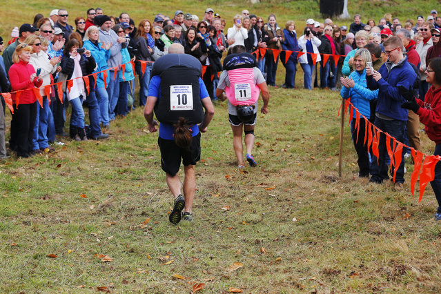Competitiors run the down hill portion of the North American Wife Carrying Championship at Sunday River ski resort in Newry, Maine October 11, 2014. REUTERS/Brian Snyder