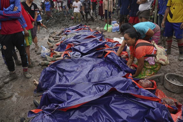 Women look at bodies shrouded in blue and red plastic sheets placed in a row on the ground Thursday, July 2, 2020 in Hpakant, Kachin State, Myanmar. At least 162 people were killed Thursday in a landslide at a jade mine in northern Myanmar, the worst in a series of deadly accidents at such sites in recent years that critics blame on the government's failure to take action against unsafe conditions. (Photo by Zaw Moe Htet/AP Photo)