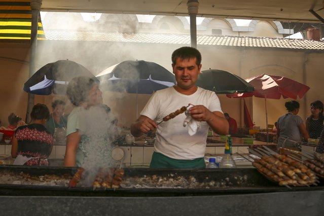 A street vendor grills kebabs at a market in Tashkent, Uzbekistan, Wednesday, August 31, 2016. (Photo by AP Photo)