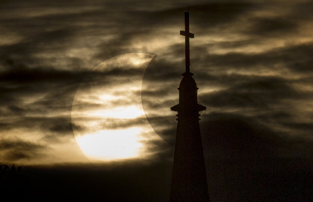 A break in the clouds reveals a partial solar eclipse behind the University of Notre Dame's Basilica of the Sacred Heart, Thursday, October 23, 2014, in South Bend, Ind. (Photo by Robert Franklin/AP Photo/South Bend Tribune)