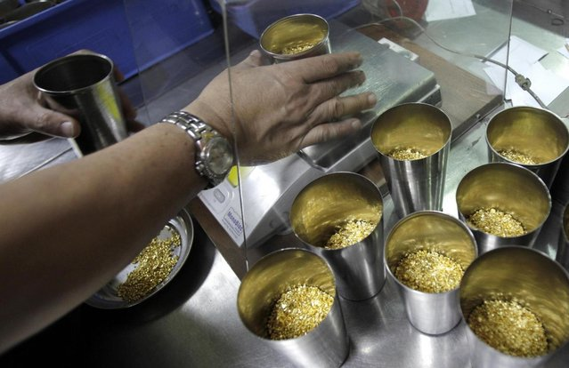 Technician prepares 1 Kg containers of gold grains for melting into 995.0 purity gold bars at the Emirates Gold refinery in Dubai, United Arab Emirates. Dubai now has about a 29 percent market share of global gold trade with nearly 1,200 tons – worth about $41 billion – changing hands annually in the city's gold markets, according to the gold industry website bullionstreet.com. At the Dubai Gold and Commodities Exchange, traders and speculators buy and sell the metal on the futures market. (Photo by Kamran Jebreili/AP Photo)