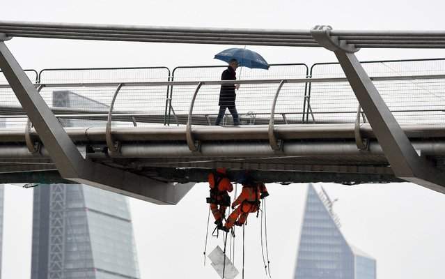 Workers make repairs on the Millennium Bridge in London, England on May 8, 2019. (Photo by James Veysey/Shutterstock)