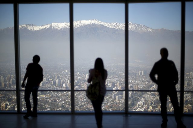 People look out to the Los Andes mountain range next to the city from a rooftop of a commercial center in a business district in Santiago, Chile, September 3, 2015. (Photo by Ivan Alvarado/Reuters)