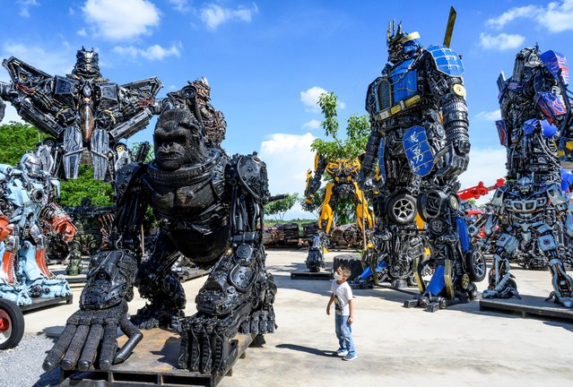 """This photograph taken on July 18, 2020 shows a child looking at a figure of King Kong in front of life-sized sculptures of characters from the """"Transformers"""" film franchise, all made of scrap metal parts, at the Ban Hun Lek museum in Ang Thong, some 100km north of Bangkok. """"Ban Hun Lek"""" or """"The House of Steel Robots"""" is a museum where a collective of artists display their scrap metal creations depicting popular comics and sci-fi film characters. (Photo by Mladen Antonov/AFP Photo)"""