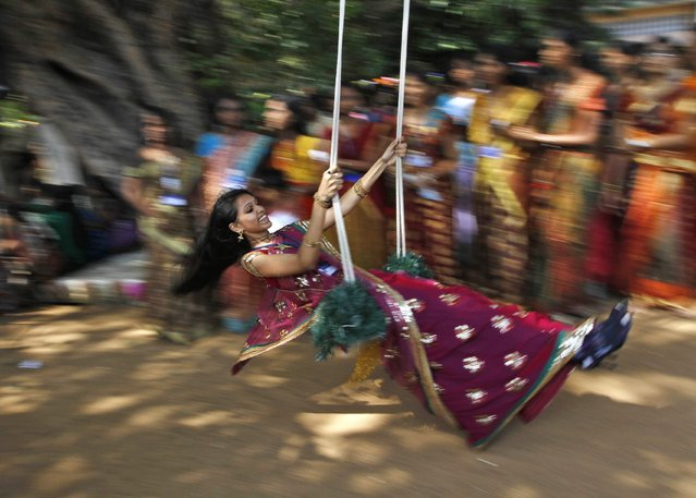 A student plays on a swing suspended from a tree inside a college complex during ongoing celebrations ahead of the south India's harvest festival of Pongal in the southern Indian city of Chennai January 12, 2013. (Photo by Babu/Reuters)
