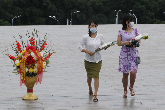 """People visit the statues of former North Korean leaders Kim Il Sung and Kim Jong Il to lay flowers on the occasion of the 67th anniversary of the end of the Korean War, which the country celebrates as the day of """"victory in the fatherland liberation war"""" in Pyongyang, Monday, July 27, 2020. (Photo by Jon Chol Jin/AP Photo)"""