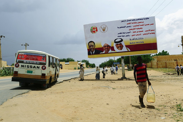 People pass a signboard during preparations for the visit of President Omar Al Bashir, Qatari Prince Sheikh Tamim bin Hamad Al Thani and Chad President Idriss Deby to support the peace process in the war torn Darfur in Al Fashir capital of North Darfur September 5, 2016. North Darfur is one of the wilayat or states of Sudan. It is one of the five states composing the Darfur region. (Photo by Mohamed Nureldin Abdallah/Reuters)