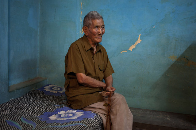 In this Wednesday, October 15, 2014 photo, Kalsang Wangdue, 85, sits on a bed in his room in New Delhi, India. Wangdue says his father was a tax collector back in Tibet and he lived a good life. He escaped into India in 1959 leaving behind his wife and son. He revisited Tibet in 1993 where his wife and son pleaded he stay back but he returned to India. He says he feels lonely especially when he falls ill and sometimes wishes he remarried. (Photo by Tsering Topgyal/AP Photo)