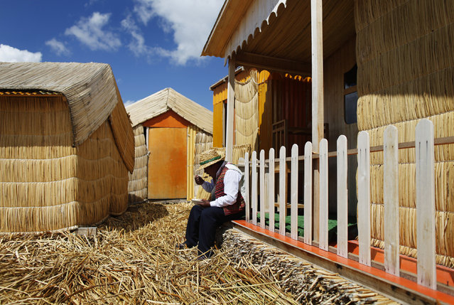 An Andean man eats outside his straw house in a Uros island at Lake Titicaca in Puno November 5, 2014. (Photo by Enrique Castro-Mendivil/Reuters)
