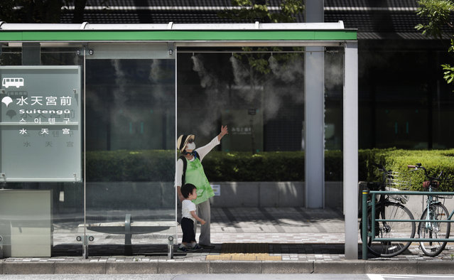 A woman wearing a face mask to protect against the coronavirus feels misting provided at a bus stop while talking with her grandson in Tokyo Thursday, August 20, 2020. (Photo by Hiro Komae/AP Photo)