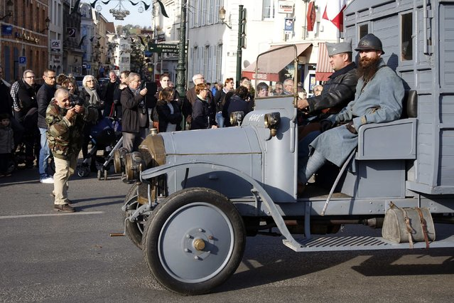 """History enthusiasts of French association """"Le Poilu de la Marne"""" drive a vintage military truck during an Armistice Day ceremony to commemorate the end of World War One at Epernay, eastern France, November 11, 2014. (Photo by Charles Platiau/Reuters)"""