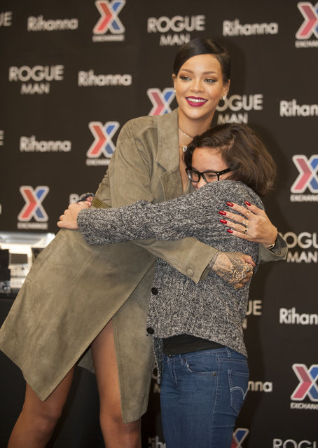 Rihanna is hugged by Anna Nunemaker during an event promoting Rogue Man at Ft. Belvoir Exchange on Wednesday, November 12, 2014 in Ft. Belvoir, Va. (Photo by Kevin Wolf/AP Photo)