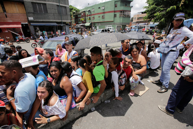 People wait in a queue to buy staple items and basic food at a sidewalk near a supermarket in Caracas, Venezuela September 14, 2016. (Photo by Henry Romero/Reuters)