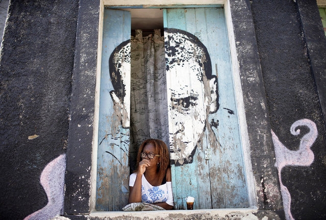 A woman looks from a window amid the new coronavirus pandemic at Morro da Providencia favela, Rio de Janeiro, Brazil, Thursday, September 3, 2020. Rio de Janeiro is deploying a program to administer 20 thousand COVID-19 quick tests in the city's poor neighborhoods to track the progress of the disease. (Photo by Silvia Izquierdo/AP Photo)