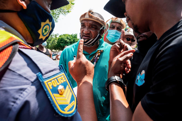 """A South African Police Service (SAPS) officer argues with a protester during a march under the banner of """"#Put South Africans First"""" outside the Nigerian Embassy in Pretoria on September 23, 2020. (Photo by Luca Sola/AFP Photo)"""
