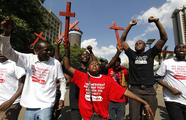 Protesters chant slogans as they carry wooden crosses, symbolising people killed in a series of attacks, during the #OccupyHarambeeAve protest in Kenya's capital Nairobi November 25, 2014. (Photo by Thomas Mukoya/Reuters)