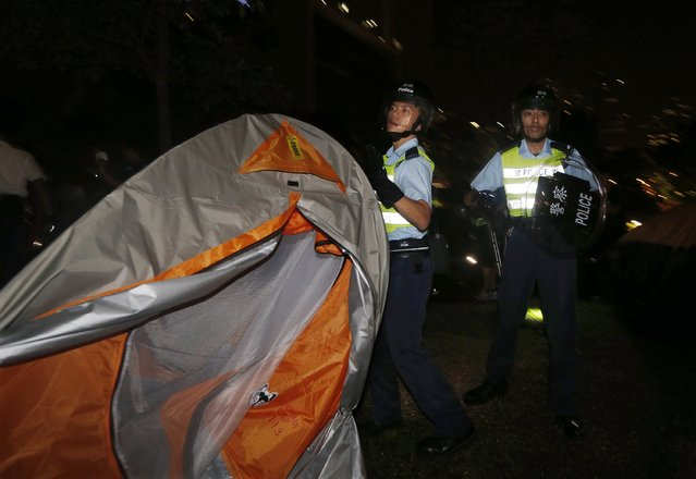 A riot policeman removes a tent set up by pro-democracy protesters at a protest site outside government headquarters in Hong Kong early December 1, 2014. (Photo by Bobby Yip/Reuters)