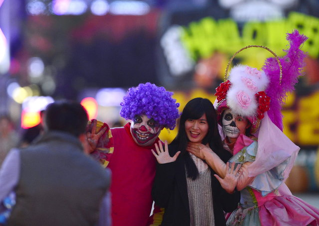 A visitor (2nd R) poses for photographs with performers in make-up and costumes during an event to celebrate the upcoming Halloween at the Happy Valley Amusement Park in Beijing, China, October 25, 2015. (Photo by Reuters/China Daily)