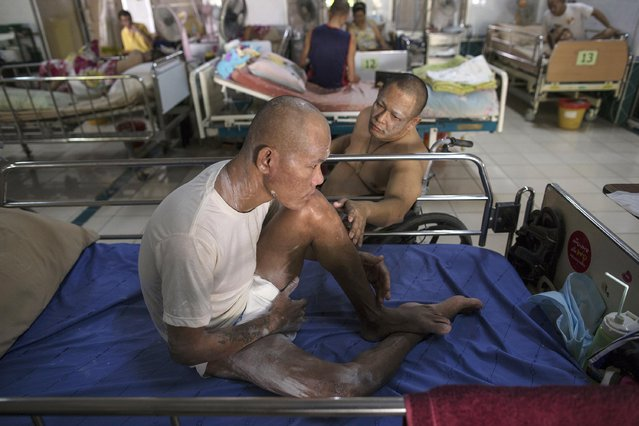 A terminally ill man is comforted by another patient in a hospice for those dying of AIDS at the Buddhist temple Wat Prabat Nampu in Lopburi province, north of Bangkok November 30, 2014. (Photo by Damir Sagolj/Reuters)