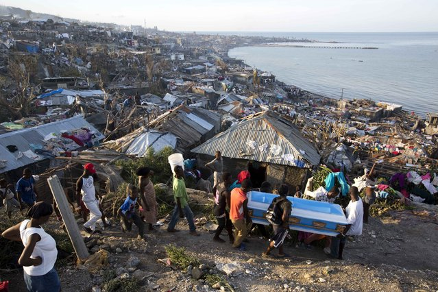 Residents carry a coffin containing the remains of a pregnant woman, a victim of Hurricane Matthew, in Jeremie, Haiti. Friday, October 7, 2016. People across southwest Haiti were digging through the wreckage of their homes Friday, salvaging what they could of their meager possessions after Matthew killed hundreds of people in the impoverished country. (Photo by Dieu Nalio Chery/AP Photo)