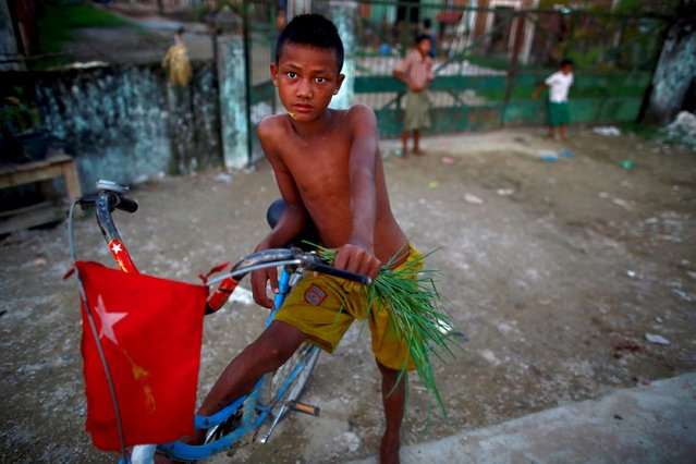A boy stands with his bike adorned with the National League for Democracy party (NLD) flag in Yangon, Myanmar on  October 22, 2015. (Photo by Soe Zeya Tun/Reuters)