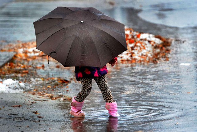 Lucy Dawes, 4, from Queensbury, N.Y., has a little fun in the rain and snowfall in Glens Falls, N.Y., Monday, November 17, 2014. (Photo by Steve Jacobs/AP Photo/The Post-Star)