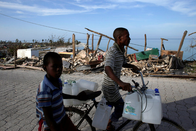 People push a bicycle as they pass next to a house destroyed by Hurricane Matthew in Port Salut, Haiti, October 9, 2016. (Photo by Andres Martinez Casares/Reuters)