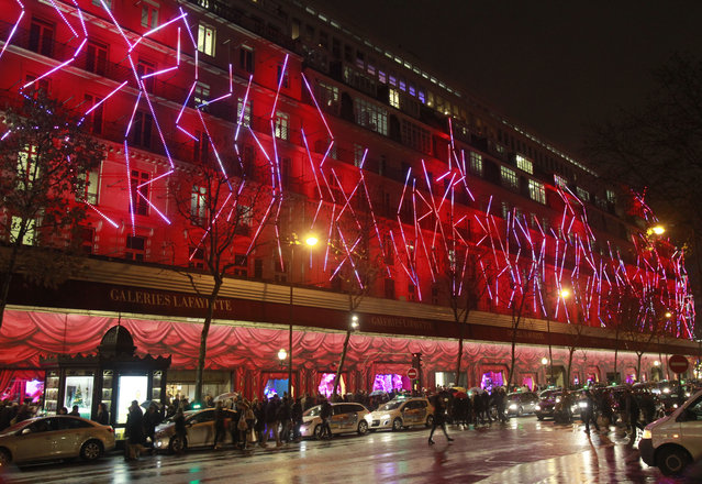 Customers overcrowd the pavement in front of the Paris main department stores, illuminated by Christmas lights,  in Paris, Wednesday December 17, 2014. (Photo by Remy de la Mauviniere/AP Photo)