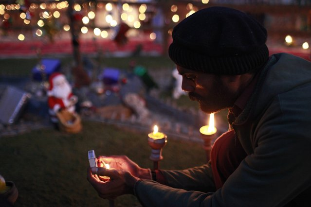 A man lights candle lamps as he offers prayer for the victims of Pakistan Taliban attack on Army Public School in Peshawar, at a nativity scene created to symbolize the birth of Jesus Christ, on Christmas eve, outside a Christian colony in Islamabad December 24, 2014. (Photo by Sara Farid/Reuters)
