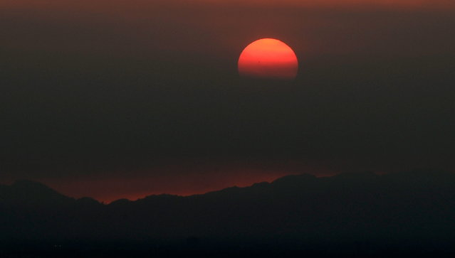 The sun sets behind smoke clouds from the Springs fire in Newbury Park and Camarillo on May 3, 2013 in Glendale, California. The fire has already spread to more than 28,000 acres and is only 20-30 percent contained. It's damaged dozens of structures and put some 4,000 people in harm's way. (Photo by Kevork Djansezian/AFP Photo)