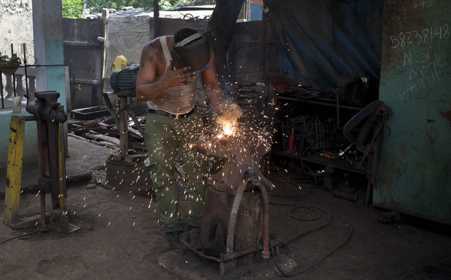 In this October 16, 2014 photo, Yoandi Failu, 34, repairs coil spring of a classic American car in Havana, Cuba. Failu fabricates parts in crude workshops. Many scavenge parts, particularly engines, from Soviet-era cars and trucks. (Photo by Franklin Reyes/AP Photo)