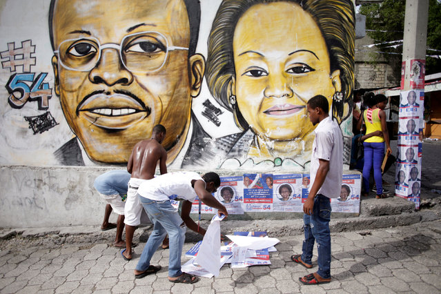 Supporters of Fanmi Lavalas political party plaster electoral posters below a painting of ousted deposed President Jean Bertrand Aristide (L) and presidential candidate Maryse Narcisse in a street of Port-au-Prince, Haiti, September 28, 2016. (Photo by Andres Martinez Casares/Reuters)