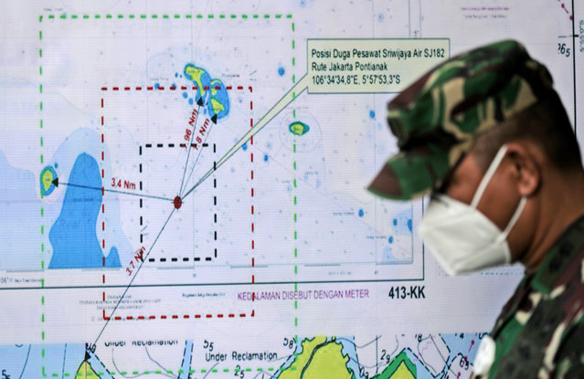 An Indonesian soldier walks past a map showing the location where a Sriwijaya Air passenger jet has lost contact with air traffic controllers shortly after taking off, at the search and rescue command center at Tanjung Priok Port in Jakarta, Indonesia, Sunday, January 10, 2021. The Boeing 737-500 took off from Jakarta for Pontianak, the capital of West Kalimantan province on Indonesia's Borneo island, and lost contact with the control tower a few moments later. (Photo by Dita Alangkara/AP Photo)