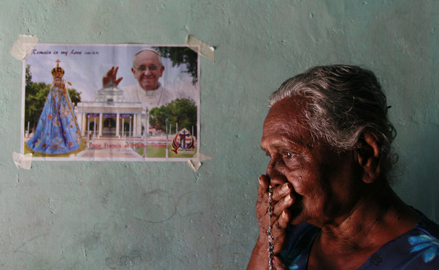 In this Wednesday, January 7, 2015 photo, a Sri Lankan Catholic devotee Rita Anthony kisses her rosary as she prays inside her house in Colombo, Sri Lanka. The Vatican has said that it hopes that Sri Lanka's Christians can play a role in helping heal the wounds of the island nation's bloody 25-year civil war, when the Tamil Tiger rebels fought to create a separate homeland in the north for the minority Tamils, who are mostly Hindu. (Photo by Eranga Jayawardena/AP Photo)