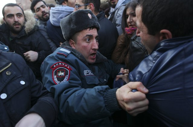 A policeman holds a protester during a rally near the Russian embassy in Yerevan, Armenia January 15, 2015. Thousands of Armenians on January 14 and 15 rallied outside the Russian embassy in Yerevan and near the Russian military base in the town of Gyumri, demanding the handover of a Russian soldier suspected of killing a family. (Photo by Hrant Khachatryan/Reuters/PAN Photo)