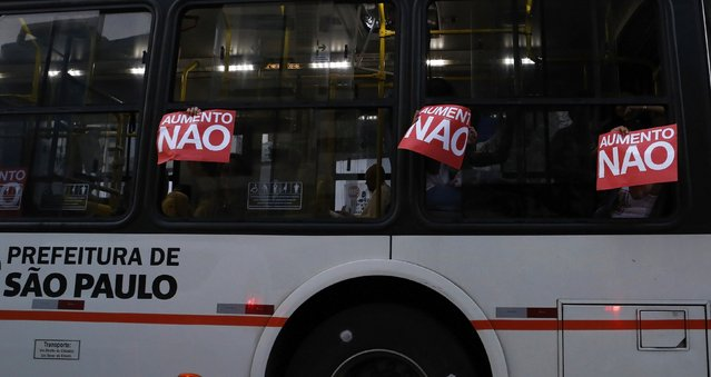 """Passengers riding inside a city bus hold up signs to the window that read, """"No to fare hikes"""", during a protest against fare hikes for city buses, subways and trains in Sao Paulo January 16, 2015. (Photo by Nacho Doce/Reuters)"""