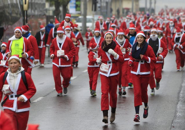Runners dressed in Santa Claus costumes take part in the Santa Claus Run in Budapest, Hungary December 6, 2015. (Photo by Bernadett Szabo/Reuters)
