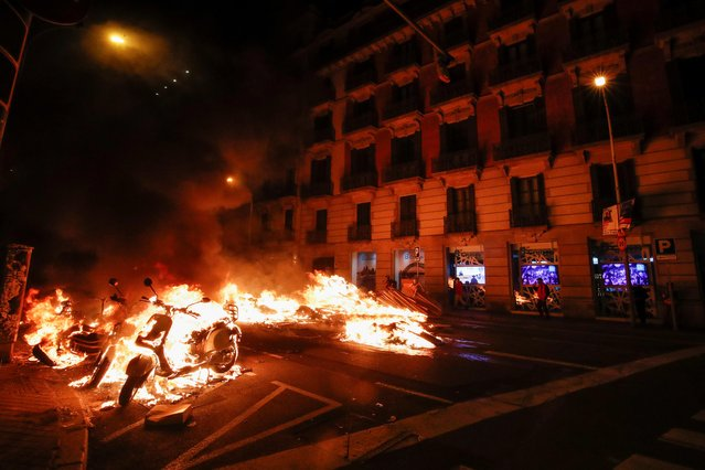 A motorbike burns during a protest against the arrest of Catalan rapper Pablo Hasel in Barcelona, Spain, February 17, 2021. (Photo by Albert Gea/Reuters)