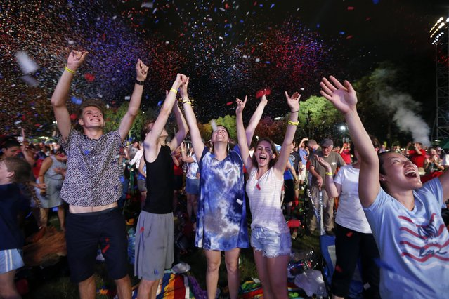 Spectators cheer as confetti falls during rehearsal for the Boston Pops Fireworks Spectacular in Boston, Tuesday, July 3, 2018. (Photo by Michael Dwyer/AP Photo)