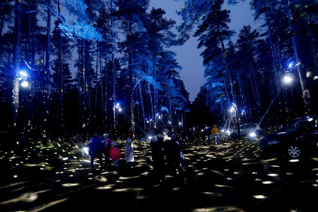 People walk in the illuminated city forest in Riga, Latvia on December 20, 2020. (Photo by Ints Kalnins/Reuters)