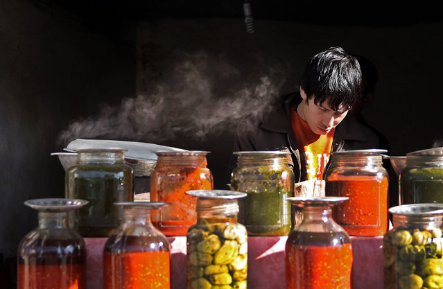 In this Tuesday, December 15, 2015 photo, an Afghan man sells traditional sauces and pickles on a street in Kabul, Afghanistan. (Photo by Massoud Hossaini/AP Photo)
