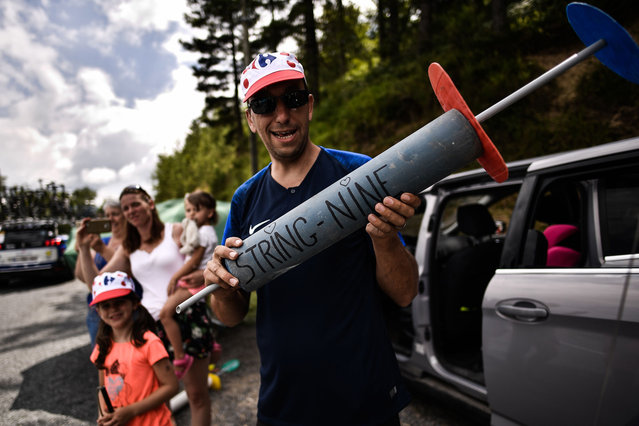 A spectator holds a makeshift giant syringe during the 15th stage of the 105th edition of the Tour de France cycling race, between Millau and Carcassonne on July 22, 2018. (Photo by Marco Bertorello/AFP Photo)